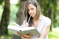 Woman reading a book at the park Stock Images
