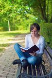 Woman reading book in the park Stock Photo