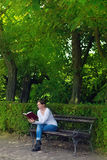 Woman reading book in the park Stock Image