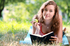 Woman reading book at park Stock Images