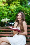 Woman reading book on park bench Royalty Free Stock Image