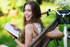 Woman reading book on park bench Stock Images