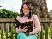 Woman Reading Book on Park Bench Stock Photo