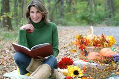 Woman reading a book in the park, fall theme Stock Photography
