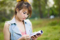 Woman reading book in park outdoors Royalty Free Stock Images