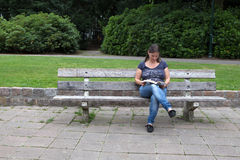 Woman reading a book in the park. Woman sitting on a bench reading a book in the park Stock Photography
