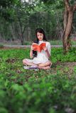 Woman reading a book in the park. Young woman reading a book in the park Royalty Free Stock Photography