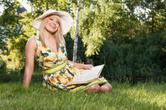 Woman reading a book in the park Stock Images