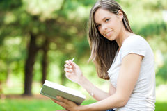 Woman reading a book at the park Stock Photo
