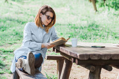 Woman reading a book in the park. Young woman reading a book in the park Royalty Free Stock Photo