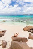 Woman reading book on picture perfect beach Anse Patates on La Digue Island, Seychelles. Royalty Free Stock Photography