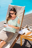 Woman reading book by pool with breakfast on table Stock Photography