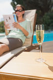 Woman reading book by pool with champagne in foreground Stock Photo