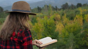 Woman reading the book. Woman in red checked shirt and hat sitting on the grass reading book at autumn forest and mountains background stock video footage