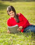 Woman Reading Book While Relaxing On Grass At Stock Photo
