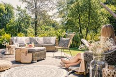 Woman reading book while relaxing at terrace with rattan furniture in the garden. Real photo stock photo