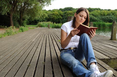 Woman reading book by river Royalty Free Stock Images