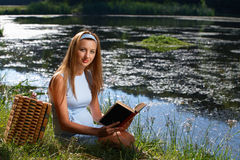 Woman reading book by the river Royalty Free Stock Photos