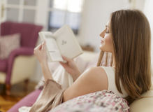 Woman reading a book in the room Stock Photos