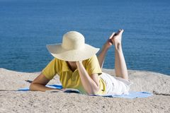 Woman reading a book at the sea Royalty Free Stock Image