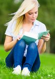 Woman reading book sits on the grass Royalty Free Stock Image