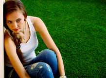 Woman reading book sits on the green grass Royalty Free Stock Photography