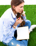 Woman reading book sits on the green grass Stock Photo