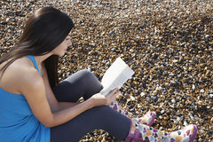 Woman Reading Book While Sitting At Beach Stock Photo