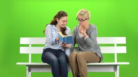 Woman and daughter is reading a book . Green screen. Woman is reading a book sitting on a bench near her daughter. Green screen stock video footage
