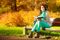 Woman reading book sitting on bench in park Royalty Free Stock Images