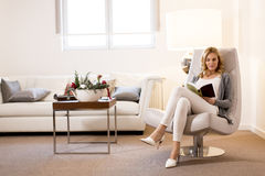 Woman reading a book and sitting on comfortable chair at home. View at young woman reading a book and sitting on comfortable chair at home Royalty Free Stock Photo