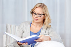 Woman reading book and sitting on couch Stock Photos