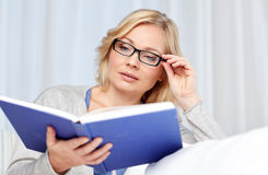Woman reading book and sitting on couch Stock Image