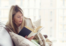 Woman reading book. While sitting cozy on couch royalty free stock photo