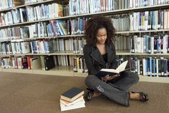 Woman Reading Book While Sitting On Floor Royalty Free Stock Photography