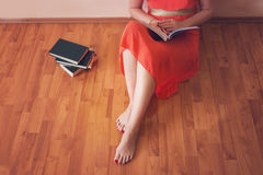 Woman reading a book. While sitting of the floor Stock Photos