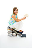 Woman reading book sitting on pile of them Royalty Free Stock Image