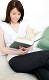 Woman reading a book sitting on a sofa Royalty Free Stock Photography