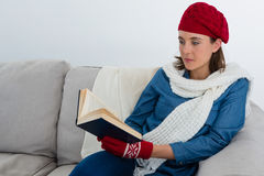 Woman reading book while sitting on sofa. Against wall at home Royalty Free Stock Images