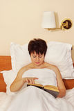 Woman reading the book before sleeping Stock Photos
