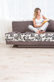 Woman reading a book and smiling as she sits on sofa in room Stock Photo