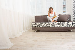 Woman reading a book and smiling as she sits on sofa in room Stock Image