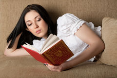 Woman Reading A Book On The Sofa Stock Photography