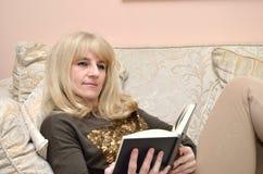 Woman Reading a Book on Sofa Stock Photos