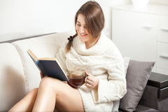 Woman reading book on sofa and drinking hot tea Stock Image