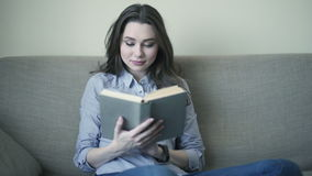 Woman reading book on sofa stock video footage
