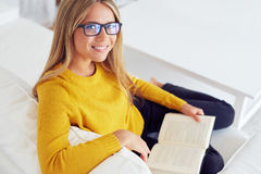 Woman reading book on sofa at home. Happy young woman reading book on sofa at home Stock Photos