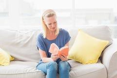 Woman reading book on sofa Stock Photos