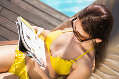 Woman reading book on sun lounger by swimming pool Royalty Free Stock Photo
