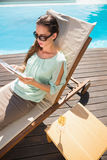 Woman reading book by swimming pool with champagne on table Stock Image